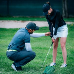 Learning golf. Golf instructor with young women on a golf course